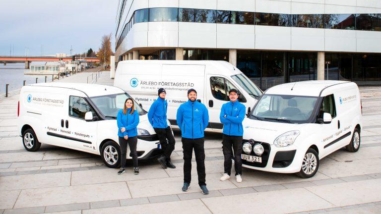 Städfirmas medarbetare står framför skåpbilar. Alla har arbetskläder. Bild tagen vid Umeå kajen