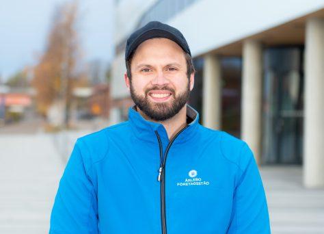 Utomhusbild på Tobias Ärlebo, VD städfirma i Umeå. Ser glad ut och har blå jacka och keps på sig